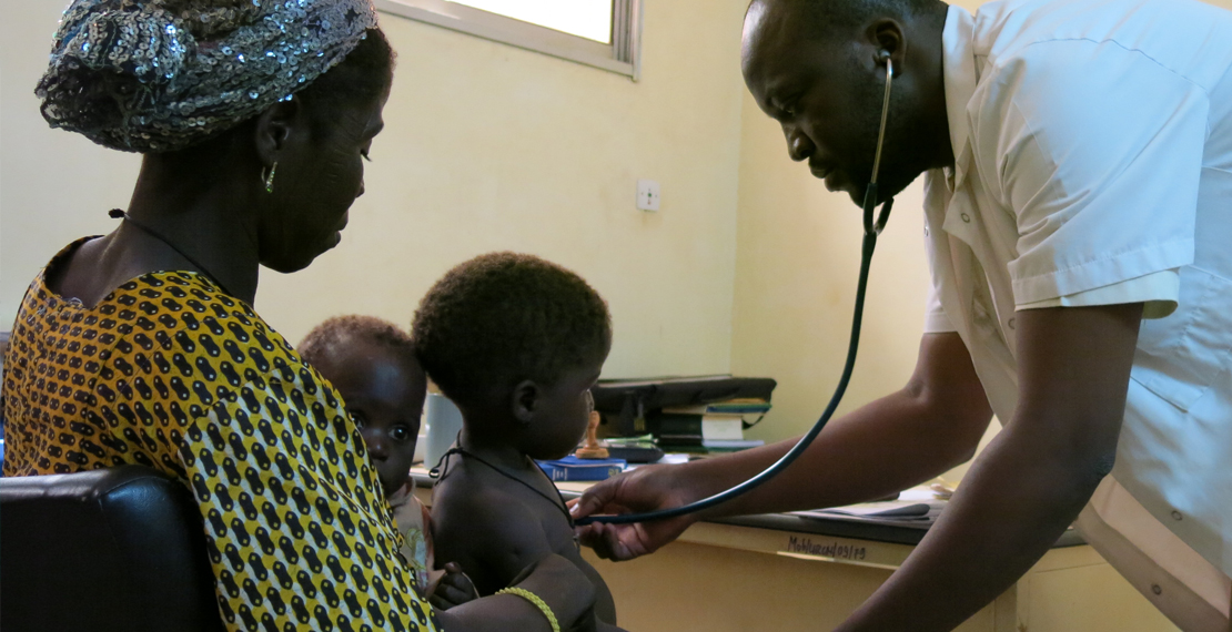 a picture of a doctor who is examining 1 of 2 children of a woman