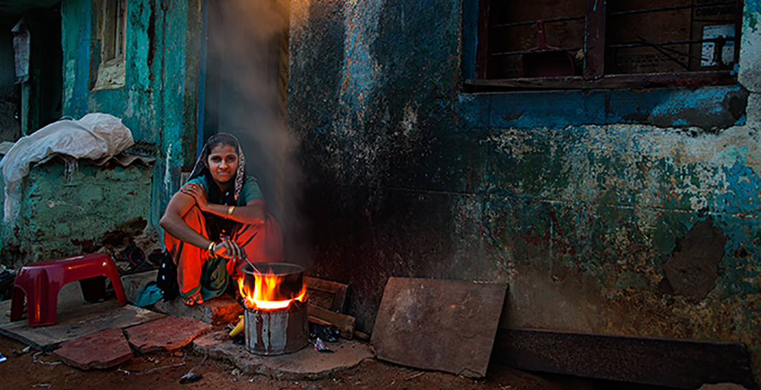 picture of a woman cooking on a fire