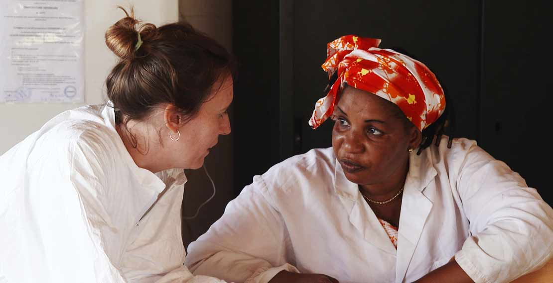 2 female health workers are shown talking to each other