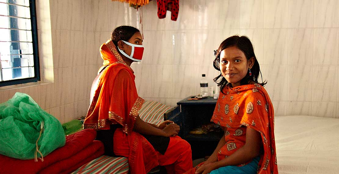 Picture of 2 women , one of which wears a mouth mask.