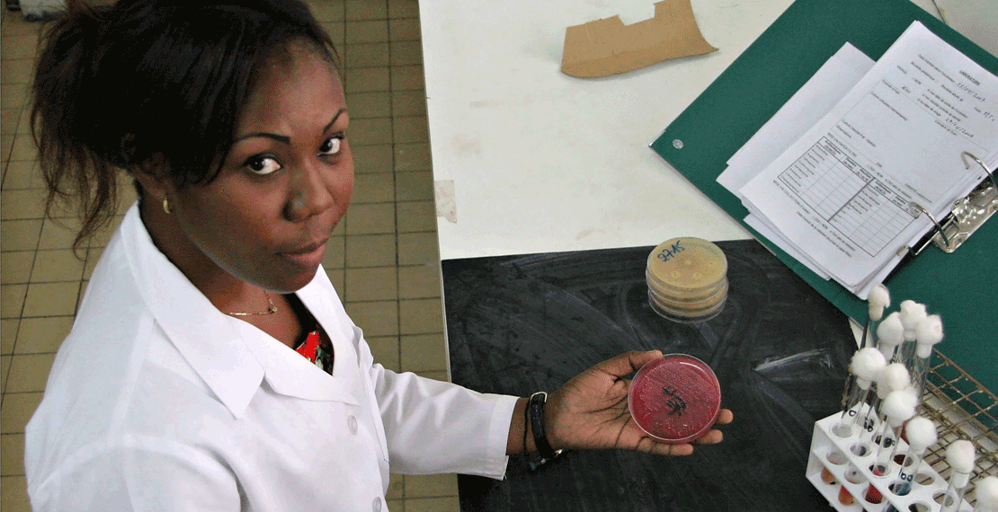 a woman in a lab coat with in her hand a filled petri dish with a sample