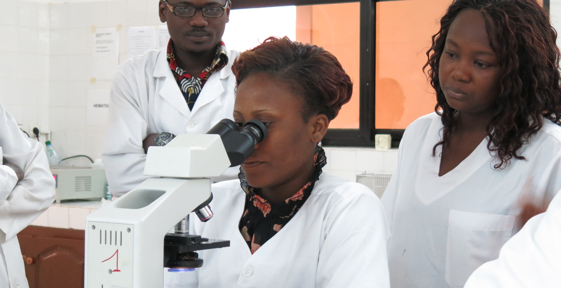 a picture of several people in a lab coat with 1 woman looking through a microscope